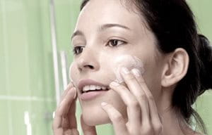 Image of woman applying Eucerin Scrub to her face.