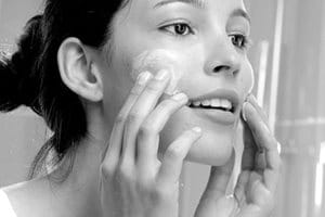 Woman applying cream on her face.