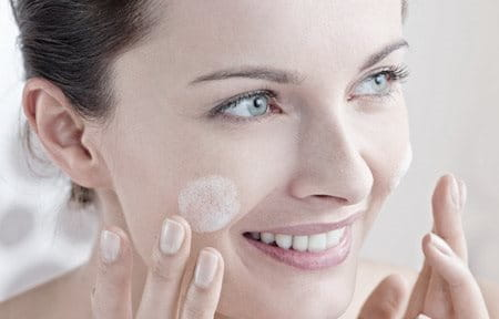 Woman applying care on her cheeks